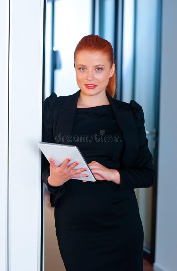 Download Femme Rouge D'affaires De Cheveux Avec Le Comprimé Dans Le Bureau Image stock - Image du bureau, regarder: 45365579