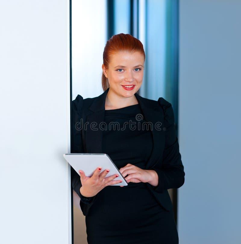 Download Femme Rouge D'affaires De Cheveux Avec Le Comprimé Dans Le Bureau Photo stock - Image du élégance, rectifié: 45365656