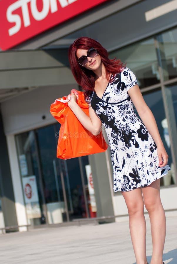 Femme rouge de cheveux avec le panier en dehors d'un magasin photo libre de droits