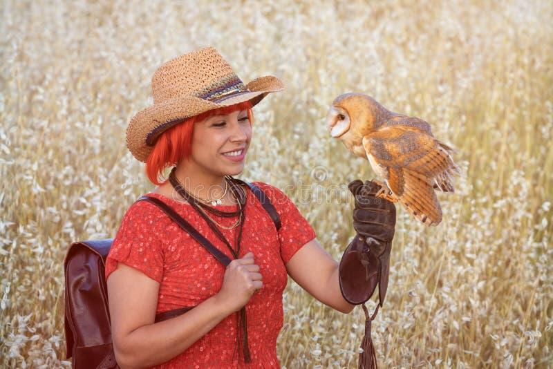 Femme rouge de cheveux avec un hibou blanc sur son bras photo stock