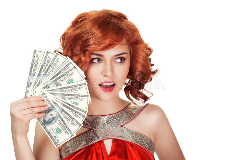 Femme rouge de cheveux jugeant des dollars disponibles photographie stock libre de droits