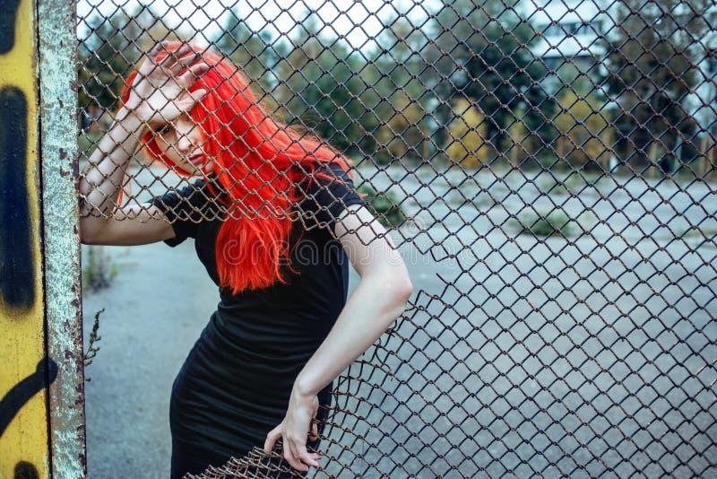 Femme rousse à la mode tenant la grille déchirée images libres de droits