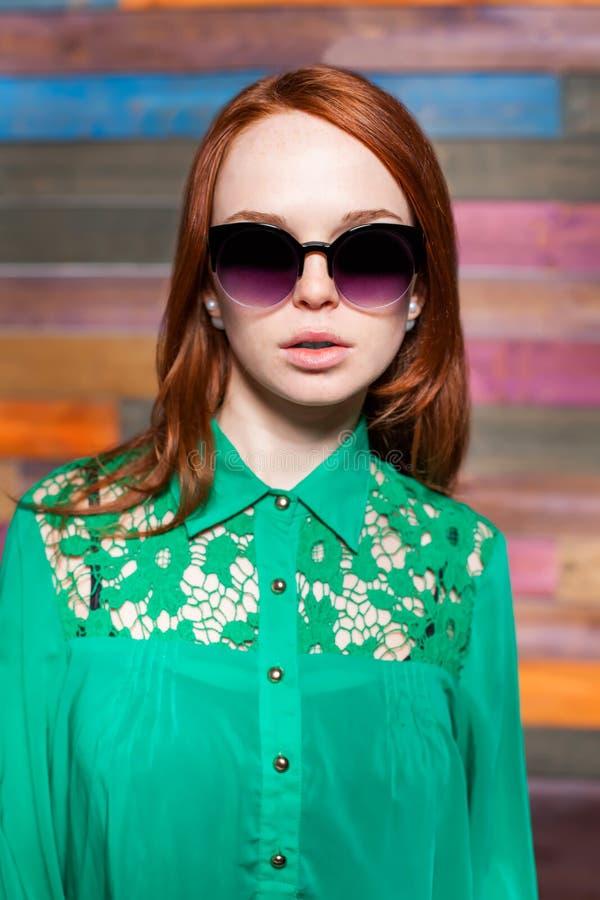 Femme rousse attirante dans des lunettes de soleil image libre de droits