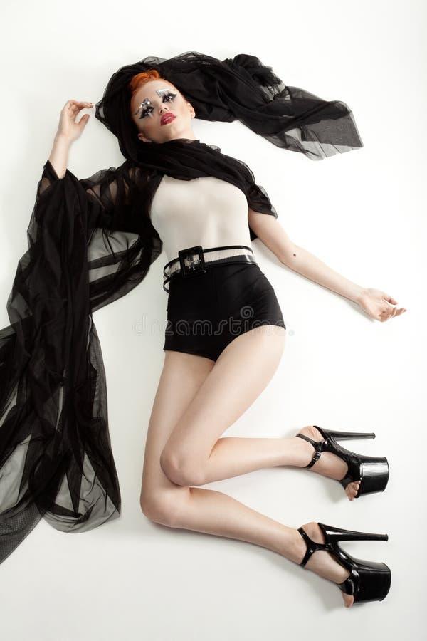 Femme rousse avec le maquillage de mode et vêtements se trouvant sur le blanc photographie stock libre de droits