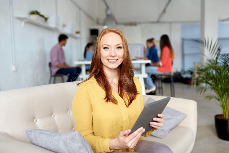 Femme rousse avec le PC de comprimé fonctionnant au bureau image stock