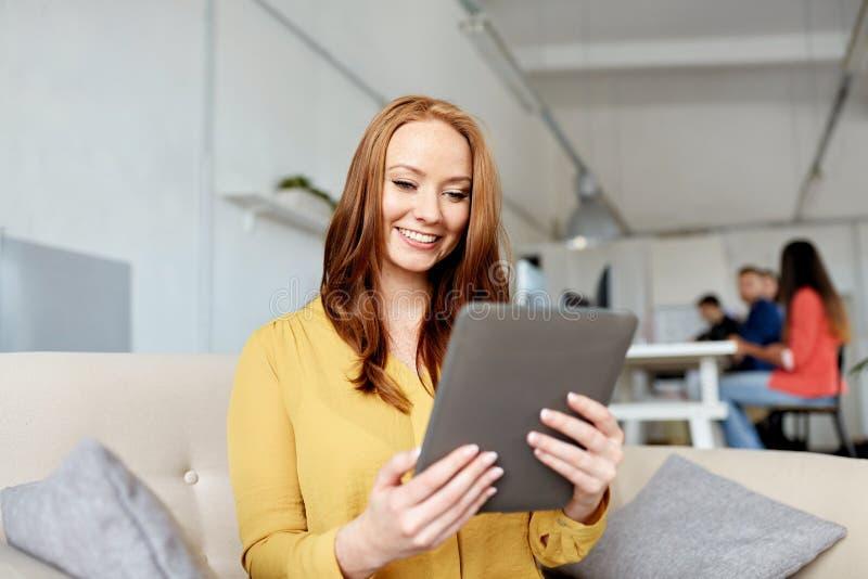Femme rousse avec le PC de comprimé fonctionnant au bureau images stock