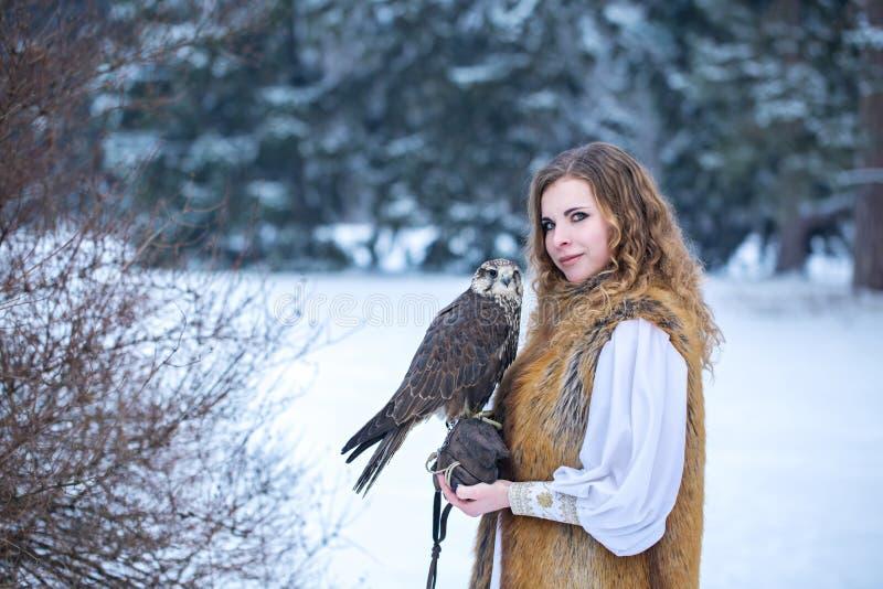 Femme rousse avec un faucon photographie stock