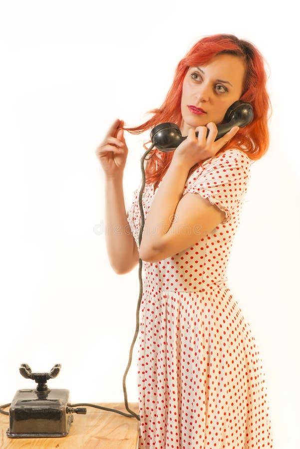 Femme rousse avec un rétro sembler parlant à un téléphone de vintage image stock