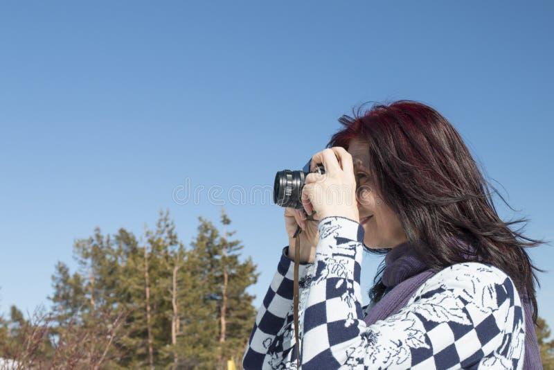 Femme rousse avec un vieil appareil-photo image stock