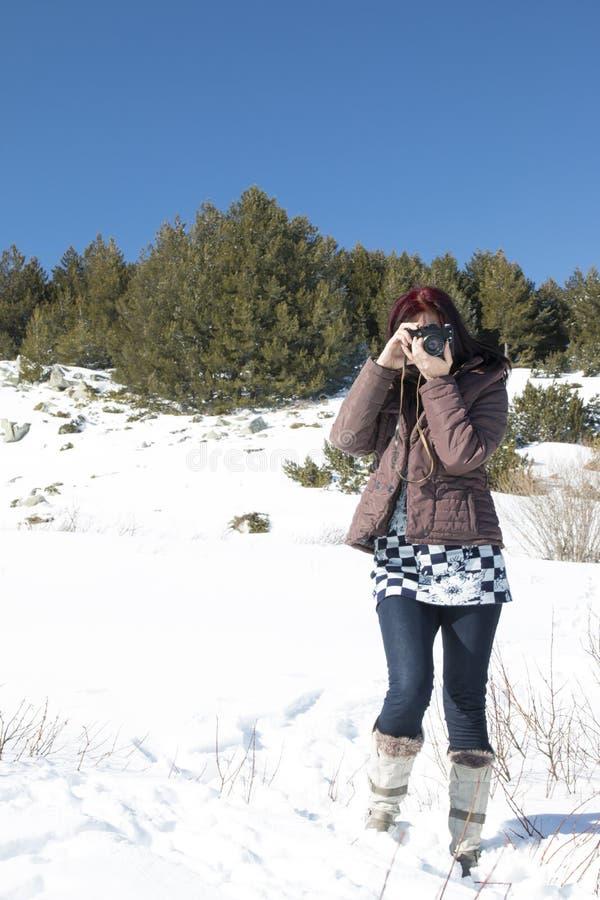 Femme rousse avec un vieil appareil-photo photographie stock libre de droits