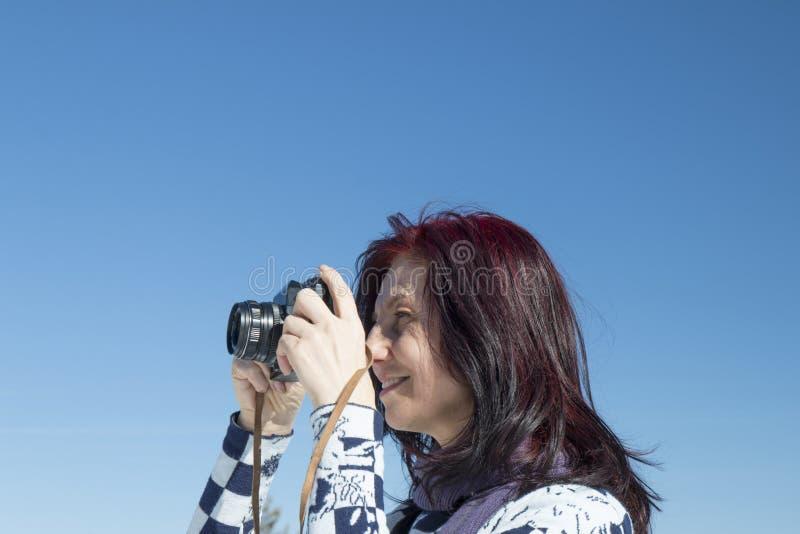 Femme rousse avec un vieil appareil-photo photo libre de droits
