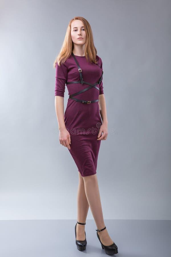 Femme rousse dans la robe de Bourgogne avec la ceinture noire se tenant dans le photostudio sur le fond gris image libre de droits