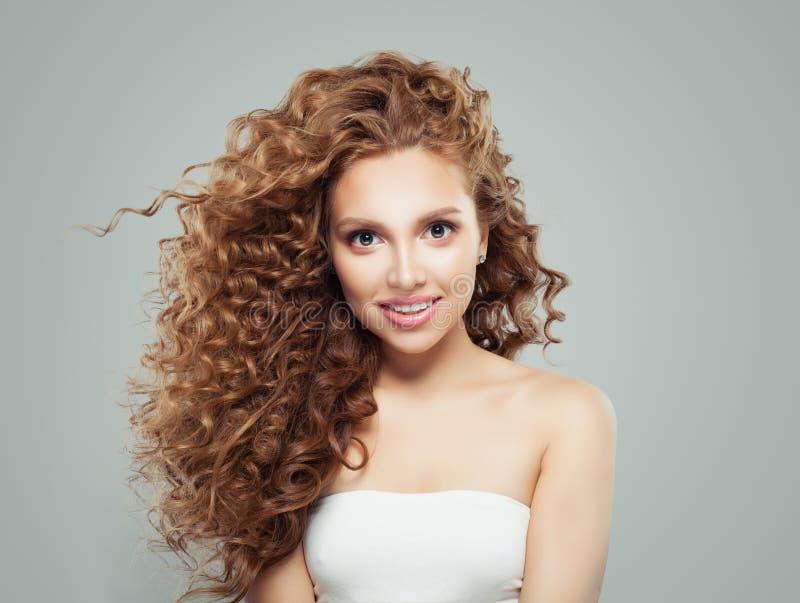 Femme rousse de sourire avec de longs cheveux bouclés sains et peau claire Fille mignonne sur le fond gris image stock