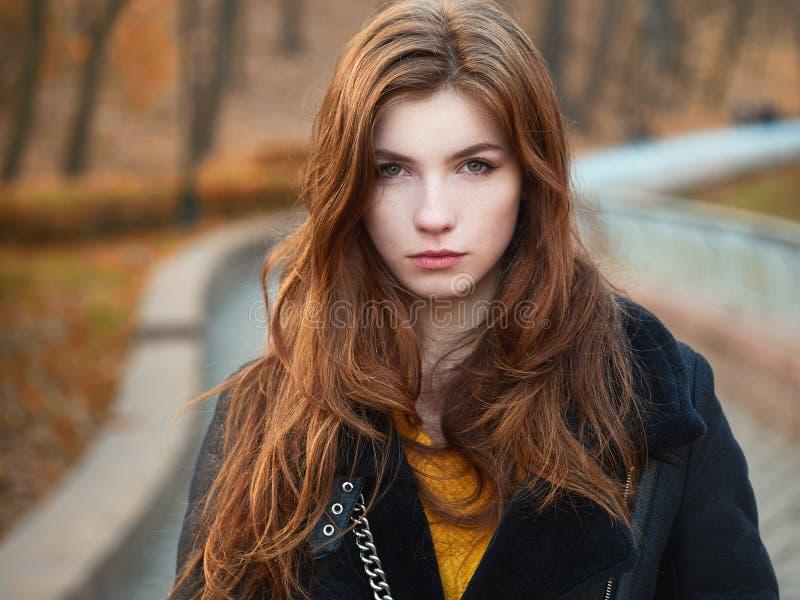Femme rousse fabuleuse avec de longs cheveux dans la veste en cuir de noir jaune de chandail sur le fond brouillé d'automne images libres de droits