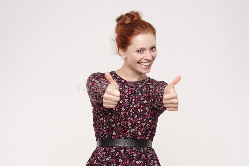 Femme rousse gaie heureuse montrant le pouce et le sourire toothy images libres de droits