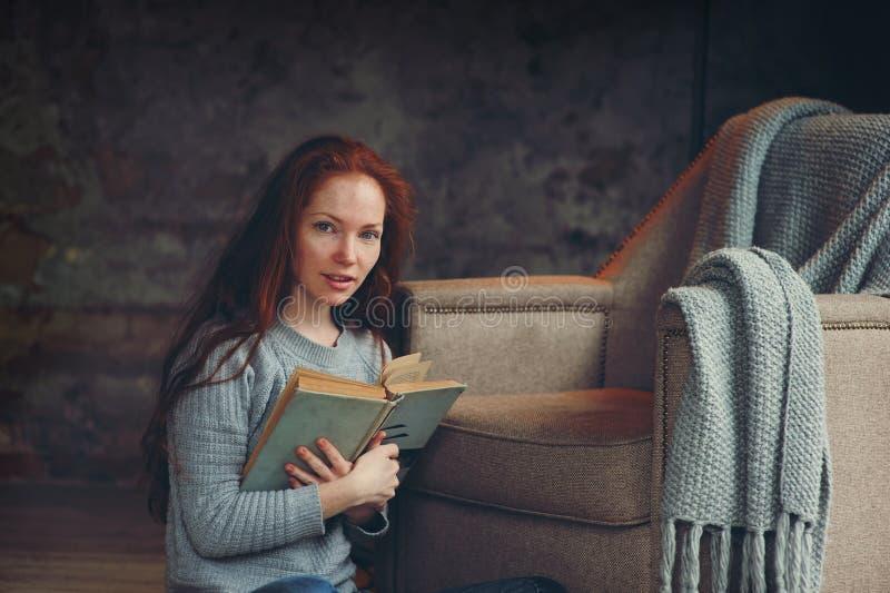 Femme rousse heureuse détendant à la maison dans le week-end confortable d'hiver ou d'automne avec le livre photographie stock
