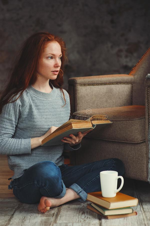 Femme rousse heureuse détendant à la maison dans le week-end confortable d'hiver ou d'automne avec le livre photos stock