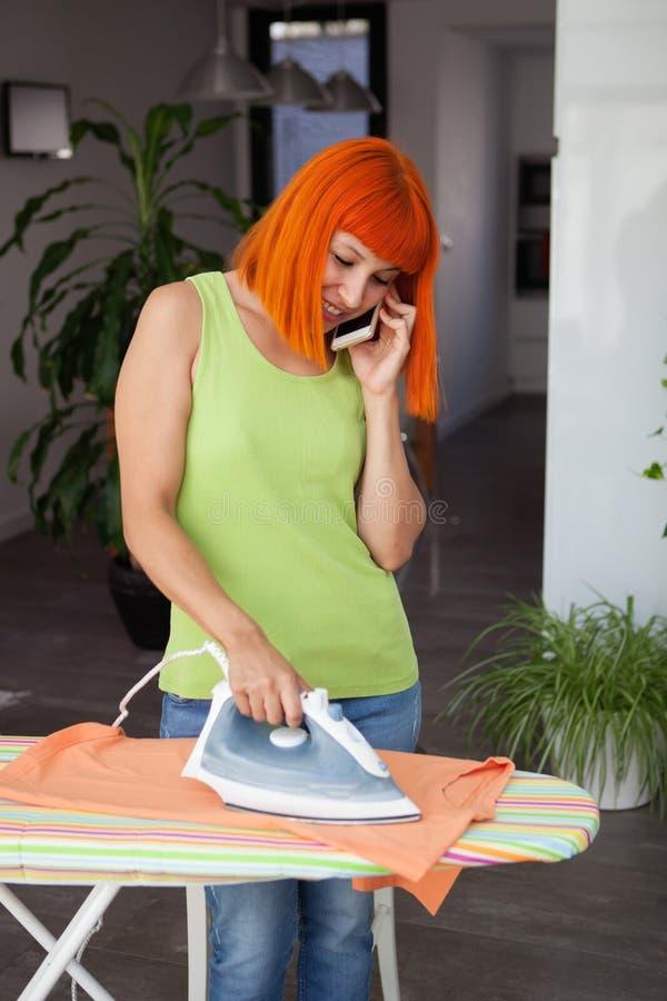 Femme rousse l vêtements repassants tout en parlant avec le mobile image stock
