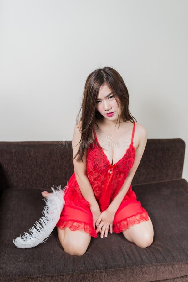 Femme rousse luxueuse dans une robe rouge sur le divan brun photos libres de droits