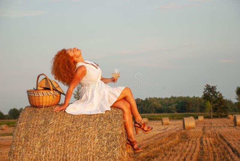 Femme rousse posant sur le champ près d'une pile de foin images libres de droits