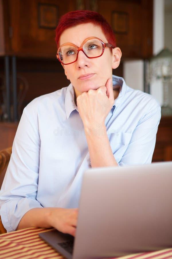 Femme rousse s'asseyant à la maison avec son ordinateur portable image stock