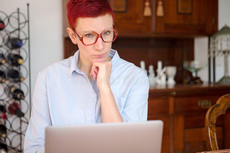 Femme rousse s'asseyant à la maison avec son ordinateur portable image libre de droits