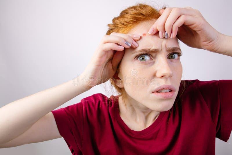 Femme rousse serrant ses boutons, enlevant le bouton de son visage photos libres de droits