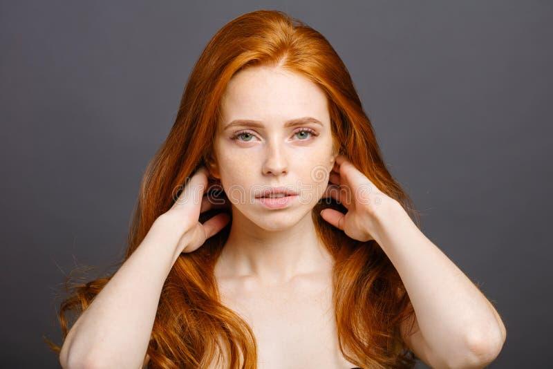 Femme rousse tenant ses cheveux sains et brillants, gris de studio photo libre de droits