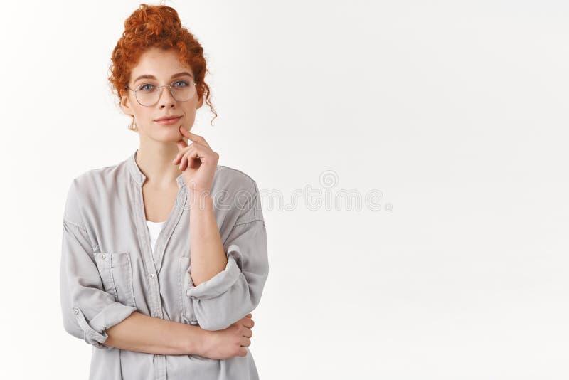 Femme rousse tendre futée avec les cheveux bouclés peignés en petit pain, regard fixe avec la caméra avec du charme de sourire, m photographie stock libre de droits