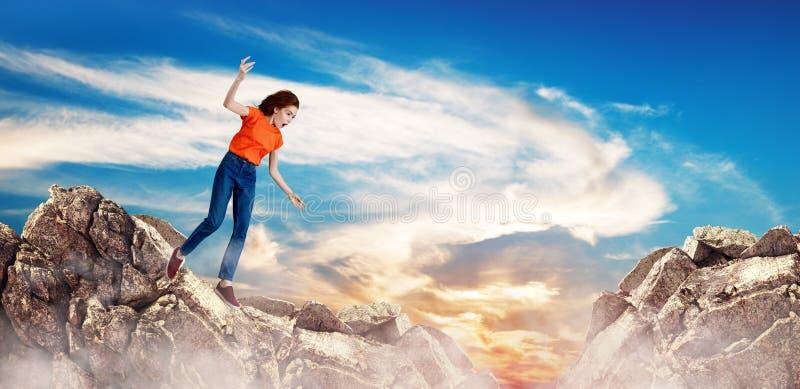 Femme rousse tombant vers le bas entre les collines sur la falaise photo stock