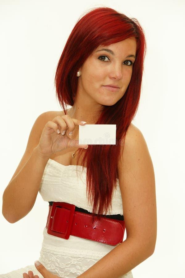 Femme roux retenant un businesscard blanc image stock