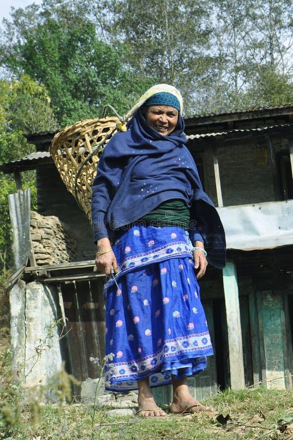 Femme rurale dans des vêtements traditionnels de couleur bleue avec un panier photos libres de droits