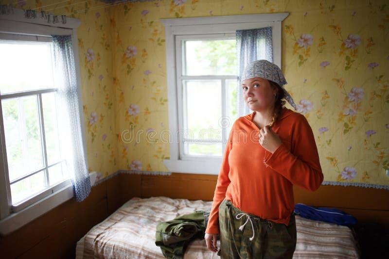 Femme russe de pays dans vêtements pour une hausse dans les bois Backround traditionnel de maison de village image libre de droits