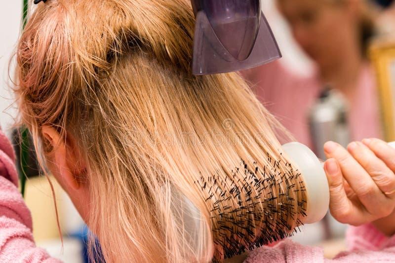Femme séchant ses longs cheveux blonds avec le sèche-cheveux et la brosse ronde images stock