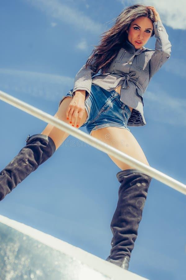 Femme séduisante chaude dans de hautes bottes noires sexy posant sur le bateau photographie stock libre de droits