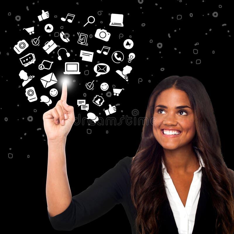 Femme sélectionnant des icônes, monde virtuel photos stock