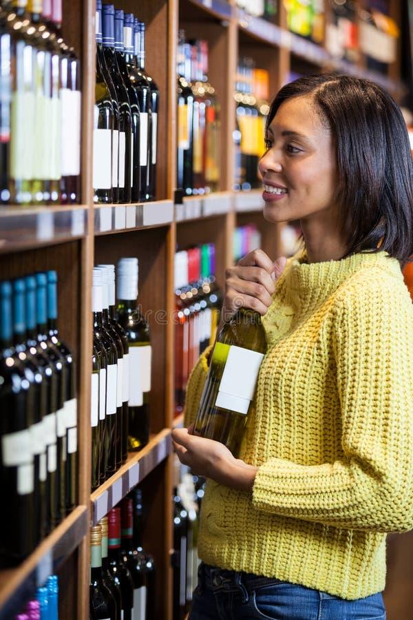 Femme sélectionnant le vin dans la section d'épicerie photographie stock libre de droits