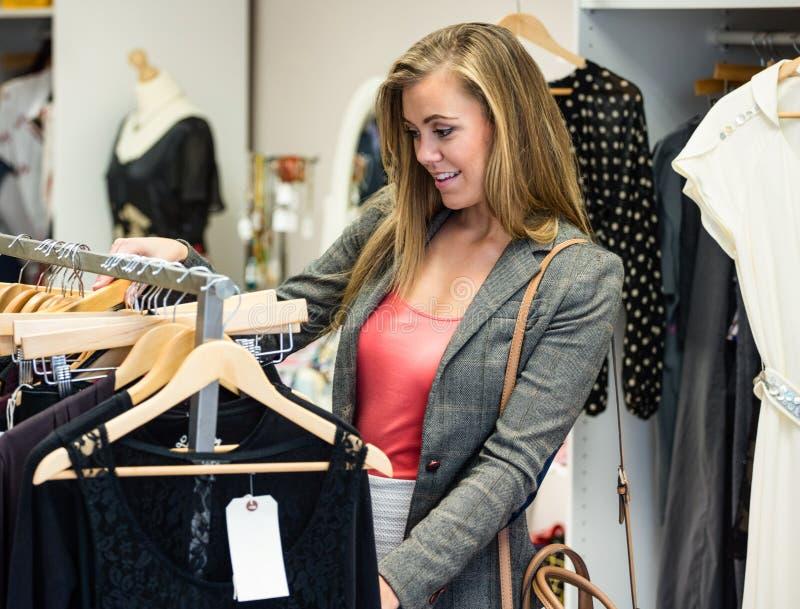 Femme sélectionnant une robe tout en faisant des emplettes pour des vêtements photographie stock libre de droits