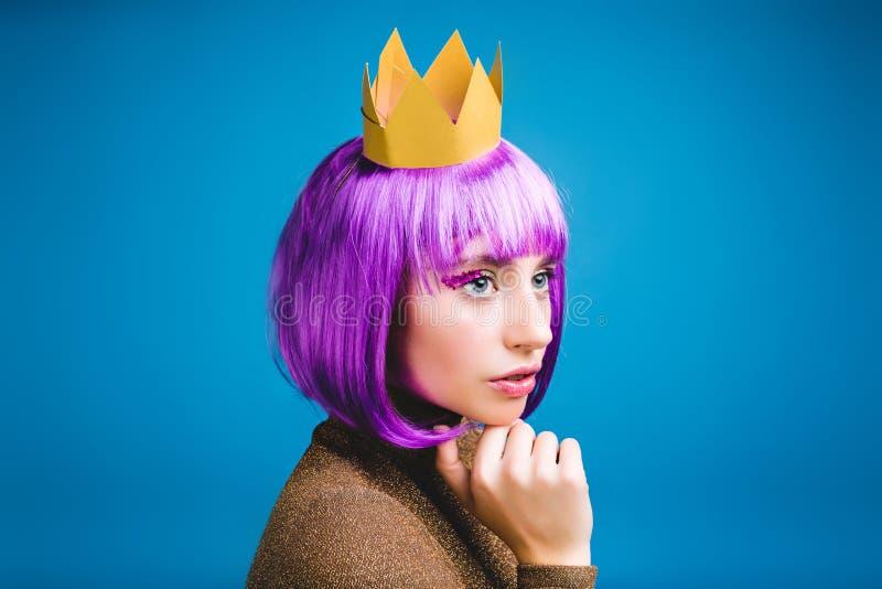 Femme sérieuse à la mode de portrait de plan rapproché jeune dans la couronne d'or sur le fond bleu Cheveux pourpres coupés, émot photo libre de droits