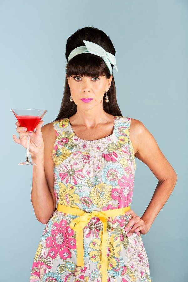 Femme sérieuse dans la robe tenant la boisson alcoolisée photographie stock libre de droits