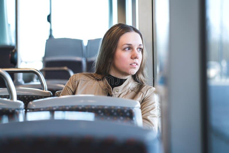 Femme sérieuse dans le train ou l'autobus regardant par la fenêtre images libres de droits