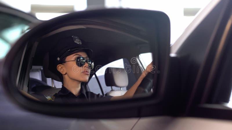 Femme sérieuse de police dans des lunettes de soleil conduisant la voiture, vue de miroir de voiture, ordre images stock