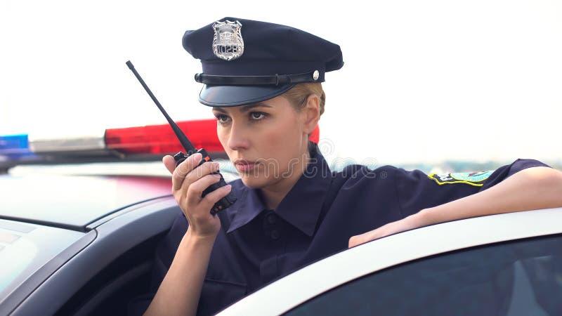 Femme sérieuse de police recevant le faire appel au poste radio, situation d'urgence, précipitation image stock