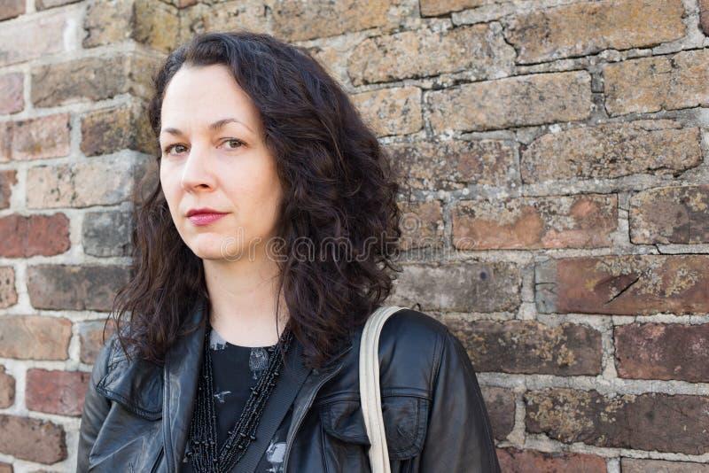 Femme sérieuse devant le vieux mur de briques images libres de droits