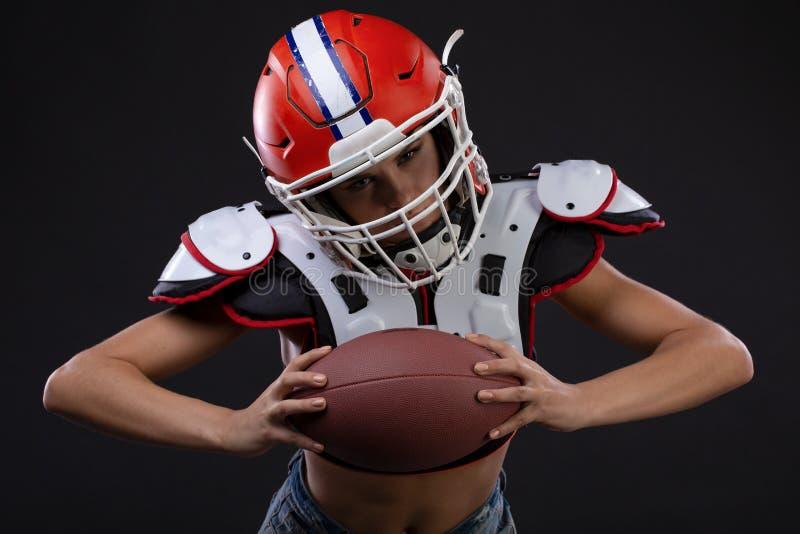 Femme sérieuse folâtre dans le casque du joueur de rugby tenant la boule et criant agressivement photos libres de droits