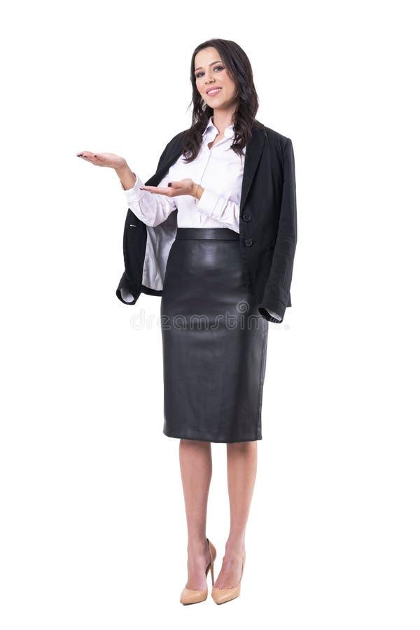 Femme s?re de sourire d'affaires avec la veste sur l'?paule pr?sentant ou montrant l'espace vide images libres de droits