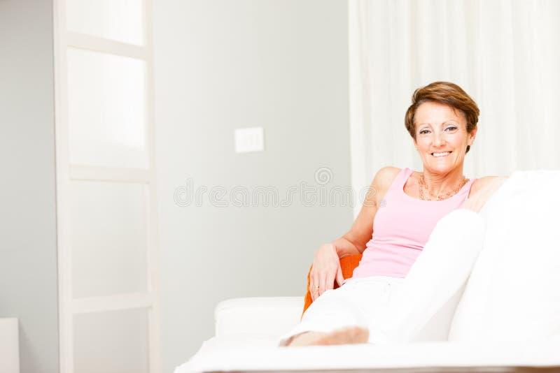 Femme sûre heureuse détendant sur un divan image libre de droits