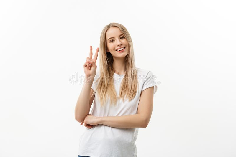 Femme sûre heureuse de portrait de plan rapproché la jeune donnant la victoire de paix, deux signent le geste, fond blanc d'isole photo stock