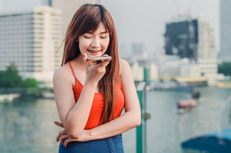 Femme sûre heureuse parlant au téléphone portable mobile sur le speakerphone au-dessus de la ville photo stock