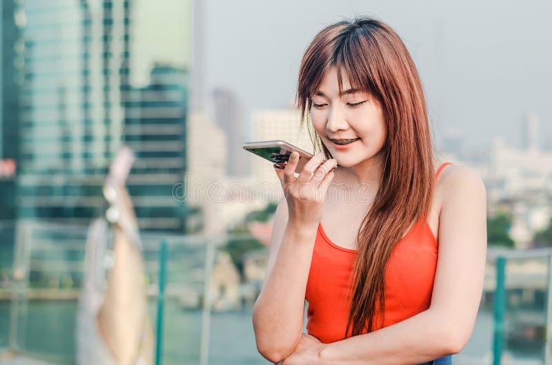 Femme sûre heureuse parlant au téléphone portable mobile sur le speakerphone au-dessus de la ville image stock